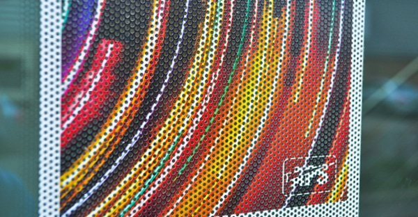 TSHO175 perforated one-way vision vinyl close-up photo of the printed film on an external window sjowing a light explosion printed image in a spectrum of reds, oranges, yellow and blues. You can clearly see the hole to vinyl ratio of the perforations in the film which allow the light through the film while still showing a great view of the colourful graphic that can only be viewed from the front, printed side.