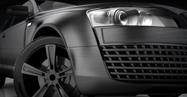 Extreme Texture Brushed Black Supreme Wrap vinyl in a close-up photo, viewed from the front right of the car and looking upwards with the brushed metal effect visible as the wrapping vinyl hugs the contours of the car shape.