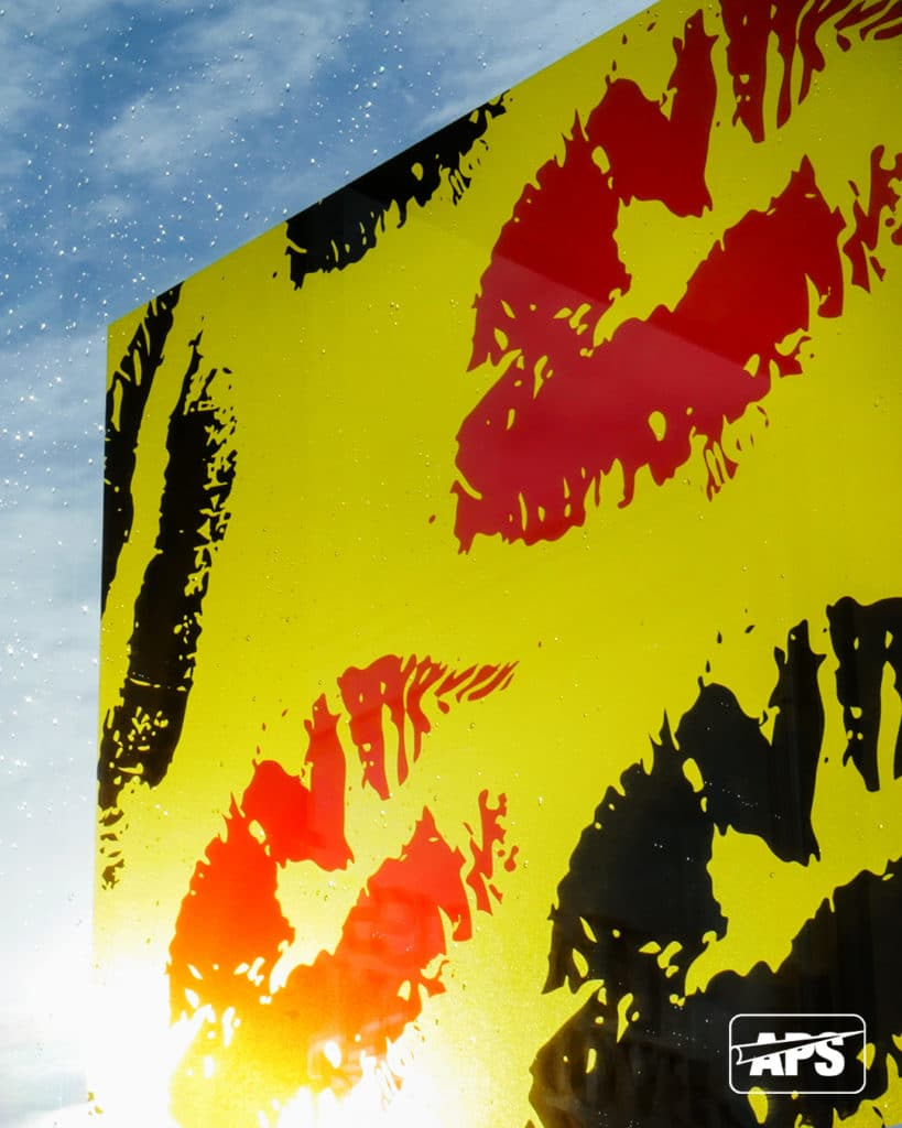JT 8300 CG-RT Yellow Dot transparent yellow window film applied as a mock-up of retail signage onto an external window with a lipstick kiss design printed in black and CMYK colour with a white ink background behind some of the red printed lips to make the colour really stand out.
