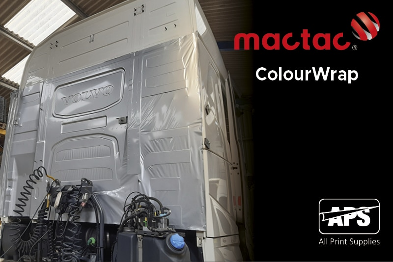 Mactac ColourWrap GM61 gloss metallic silver CAD wrapping film in the process of being applied to wrap the entire truck cabin of a Volvo Truck and is halfway through being applied into the contours of the deeply recessed areas at the back of the cab with the indented Volvo logo prominent and a higly visible feature.